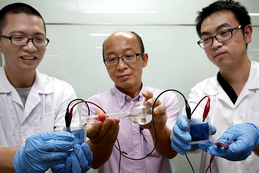 Nanyang Technological University (NTU) scientists (from left) Zheng Ke, Professor Sun Xiao Wei and Liu He have developed a smart window which can darken or brighten without the need for an external power source. -- ST PHOTO:LAU FOOK KONG
