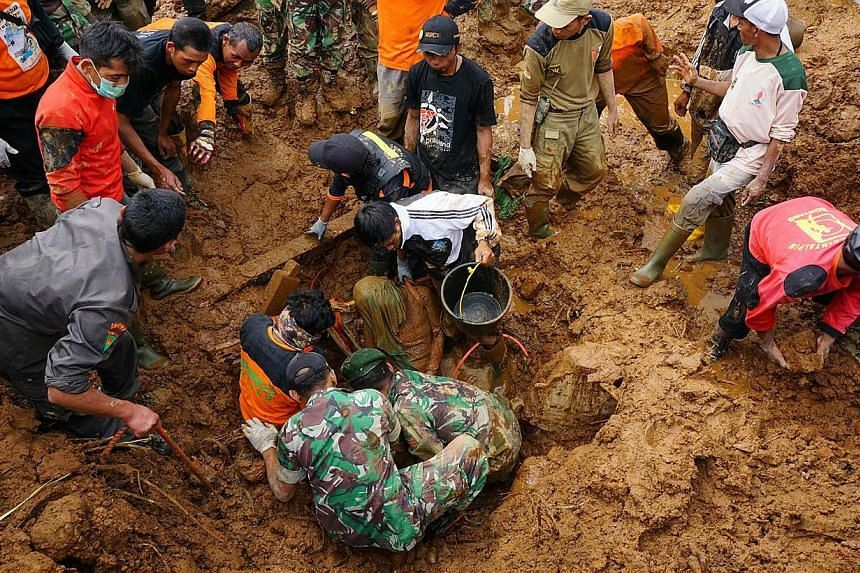 Members of a search and rescue team remove the body of a victim of a landslide at the Jemblung village in Banjarnegara in central Java on Sunday. PHOTO: AFP