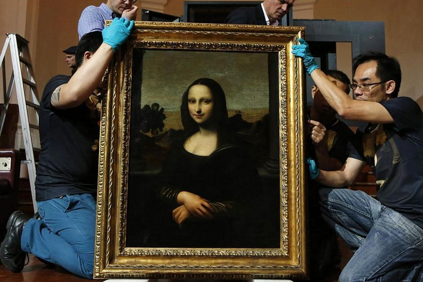 Movers prepare to hang Leonardo da Vinci's 'Early Mona Lisa' painting ahead of its exhibition at The Arts House in Singapore in this file picture taken last week. -- PHOTO: REUTERS