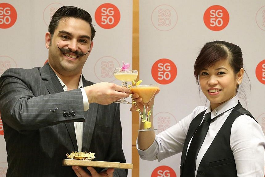 Head bartender from Regent Singapore, Ricky Paiva (left), 33, and head bartender from Grand Hyatt Martini Bar, Rosanna Mercado (right), 29, pose with their winning cocktail and mocktail - Singapura Nacional and Golden Harvest - respectively. -- ST PH