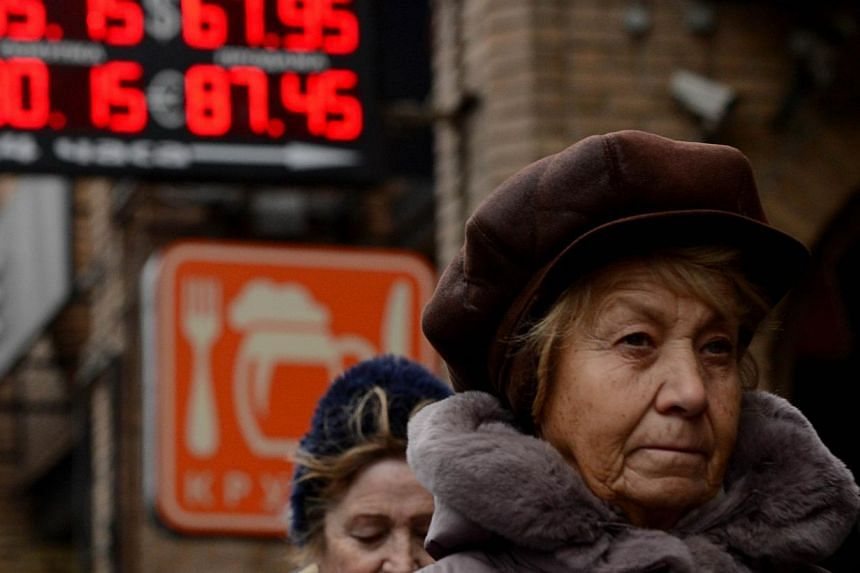 Pedestrians walk past a board listing foreign currency rates against the Russian rouble outside an exchange office in central Moscow on Dec 16, 2014. The Russian rouble set a new all-time record low on Tuesday after bouncing back briefly despite an e