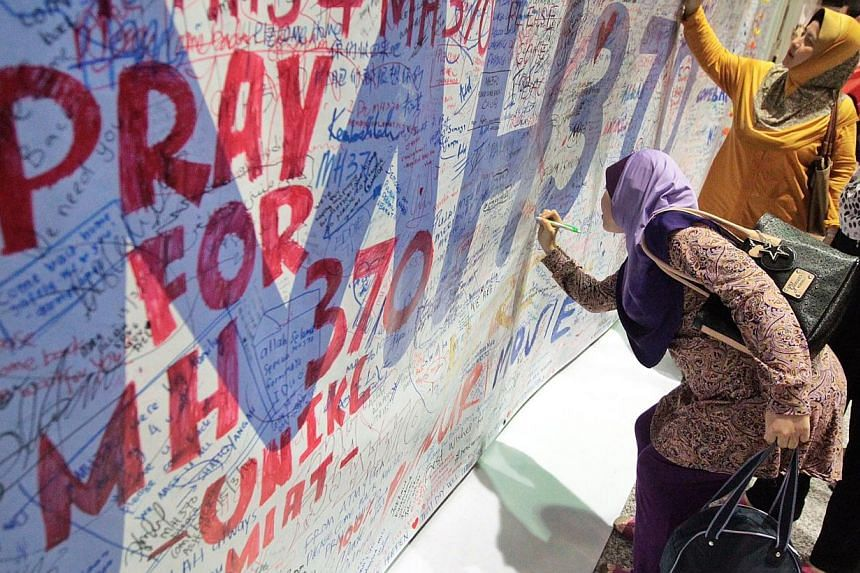 Well-wishers signing messages of hope and support for the families of those on board the missing Malaysia Airlines (MAS) flight MH370 at the KL International Airport (KLIA) Observation Deck on Mar 16, 2014. -- PHOTO: ST FILE