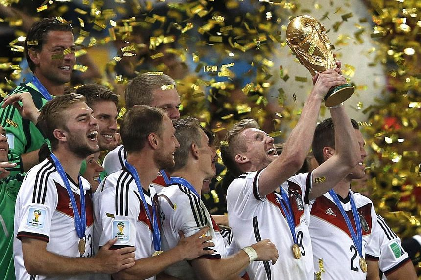 Germany's forward Andre Schuerrle (middle) holds the trophy as he celebrates with teammates after his team's victory in the final football match between Germany and Argentina for the FIFA World Cup at The Maracana Stadium in Rio de Janeiro on July 13