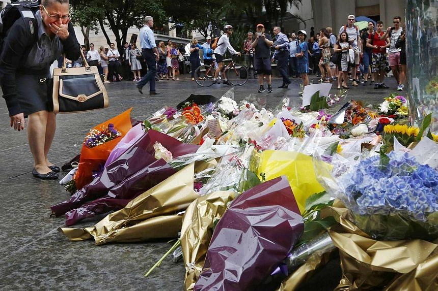 A woman reacts after placing a floral tribute for those who died in the Sydney cafe siege, near the site of the incident, in Martin Place on Dec 16, 2014. -- PHOTO: REUTERS