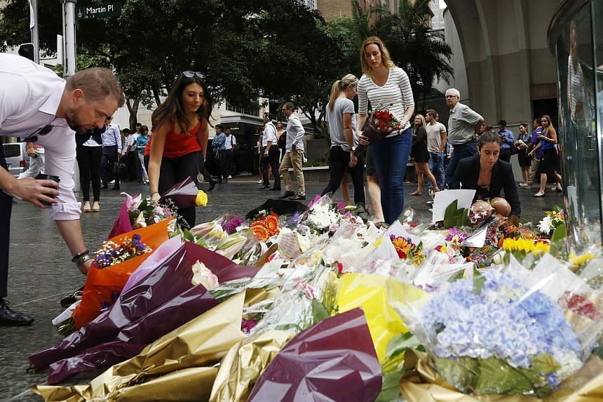 Mourners lay floral tributes to those who died in the Sydney cafe siege, near the site of the incident, in Martin Place. -- PHOTO: REUTERS