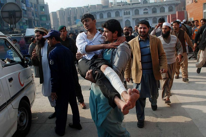 A man carries a student, who was injured during an attack by Taleban gunmen on the Army Public School, after he received treatment at a hospital in Peshawar on Dec 16, 2014. -- PHOTO: REUTERS
