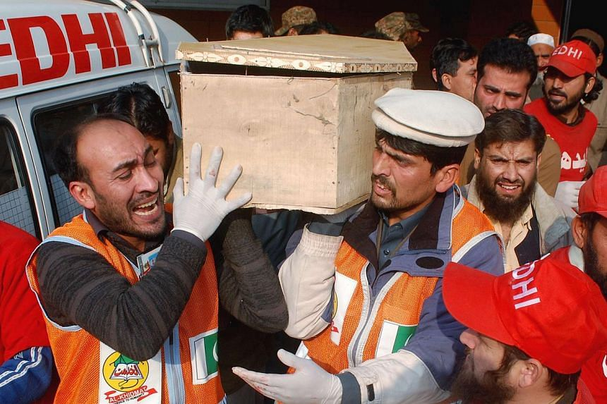 Rescue workers and family members carry the coffin of a student, who was killed during an attack by Taleban gunmen on the Army Public School, in Peshawar on Dec 16, 2014.-- PHOTO: REUTERS
