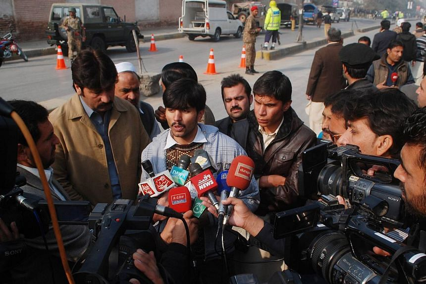 The media interview a man, who was rescued from the Army Public School that in under attack by Taleban gunmen, in Peshawar, December 16, 2014.-- PHOTO: REUTERS
