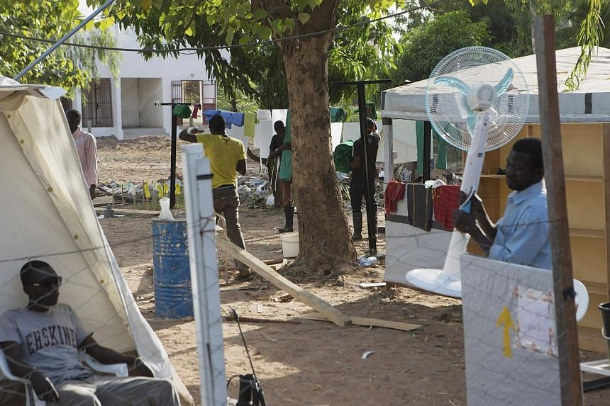 A man brings a fan into an Ebola treatment center in Bamako, Mali, on Nov 13, 2014. Border closures, quarantines and crop losses in West African nations battling the Ebola virus could lead to as many as one million people going hungry, UN food a