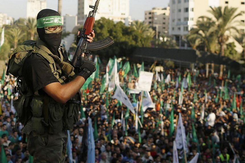 """A Hamas militant celebrates with people what they said was a victory over Israel, in Gaza City in this Aug 27, 2014 file photo.The EU said on Wednesday, Dec 14, 2014, that it still considers Hamas to be a """"terrorist"""" group even though a Europea"""