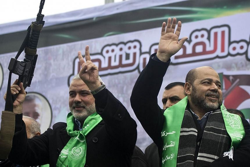 Gaza Hamas leaders Ismail Haniya (left) and Mussa Abu Marzuq brandish a weapon as they greet supporters during a parade marking the 27th anniversary of the Islamist movement's creation on Dec 14, 2014 in Gaza City. The Palestinian Islamic militant