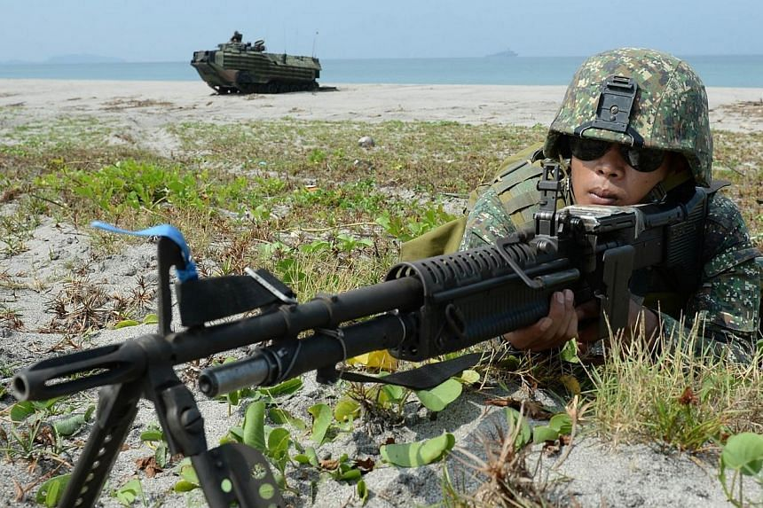 """Philippine Marines take their positions next to an amphibious assault vehicle (AAV) of the US marines 31st Marine Expeditionary Unit based in Okinawa Japan, as part of the 12-day US and Philippine annual joint naval exercise dubbed """"Phiblex"""" along th"""