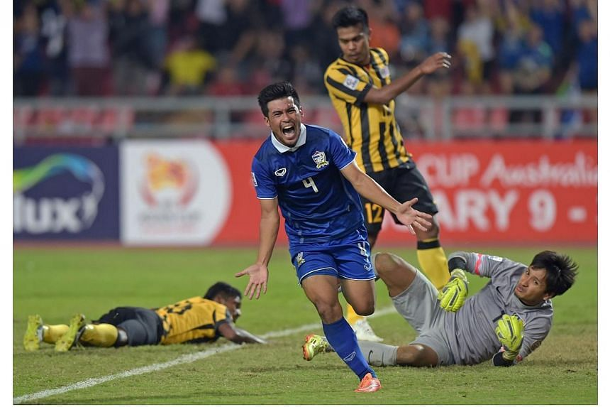 Kroekrit Thawikan of Thailand (centre) celebrates after scoring against Malaysia during their final 1st leg football match of the Suzuki Cup 2014 at the Rajamangala stadium in Bangkok on Dec 17, 2014. Thailand won 2-0. -- PHOTO: AFP