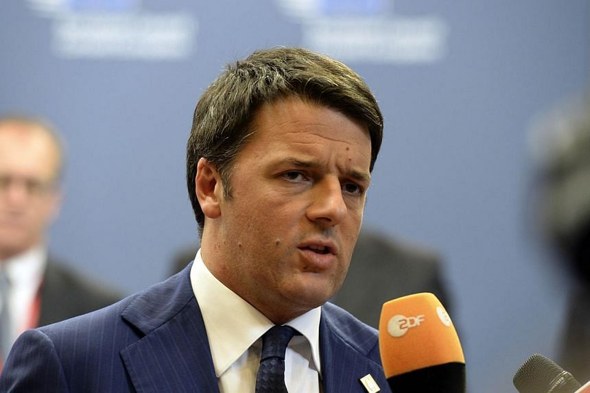 Italian Prime Minister Matteo Renzi talks to the media on Oct 24, 2014 at the end of a European summit at EU headquarters in Brussels. Mr Renzi has vowed to cut the towering debt pile of the eurozone's fifth-largest economy. -- PHOTO: AFP