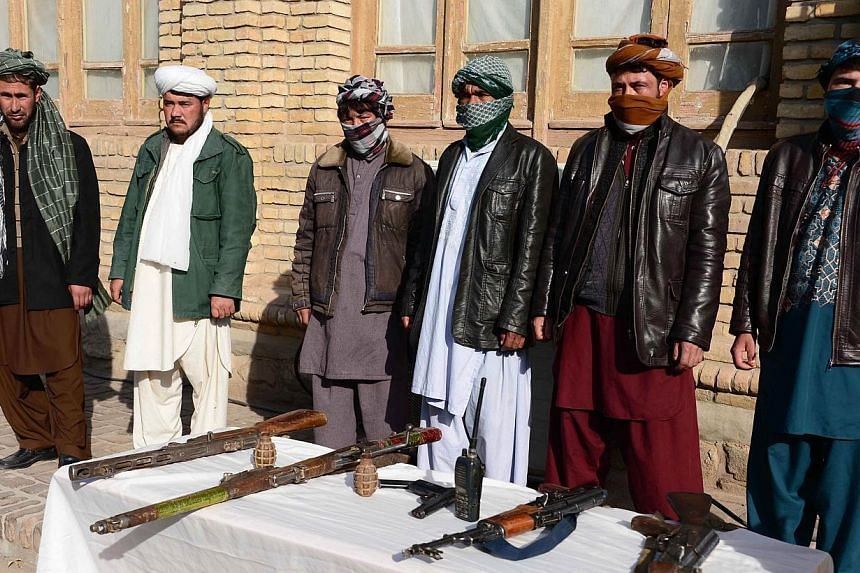 Former Taleban fighters stand with their weapons during a reconciliation process in Herat province on Nov 22, 2014. -- PHOTO: AFP
