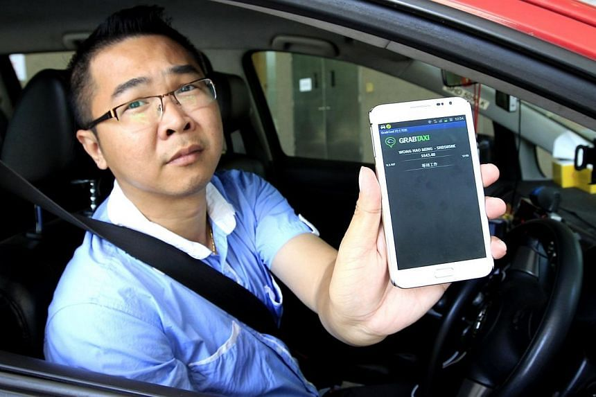 Taxi driver Wong Hao Min with his mobile app, GrabTaxi, which helps him find passengers and boost his earnings. -- PHOTO: ST FILE