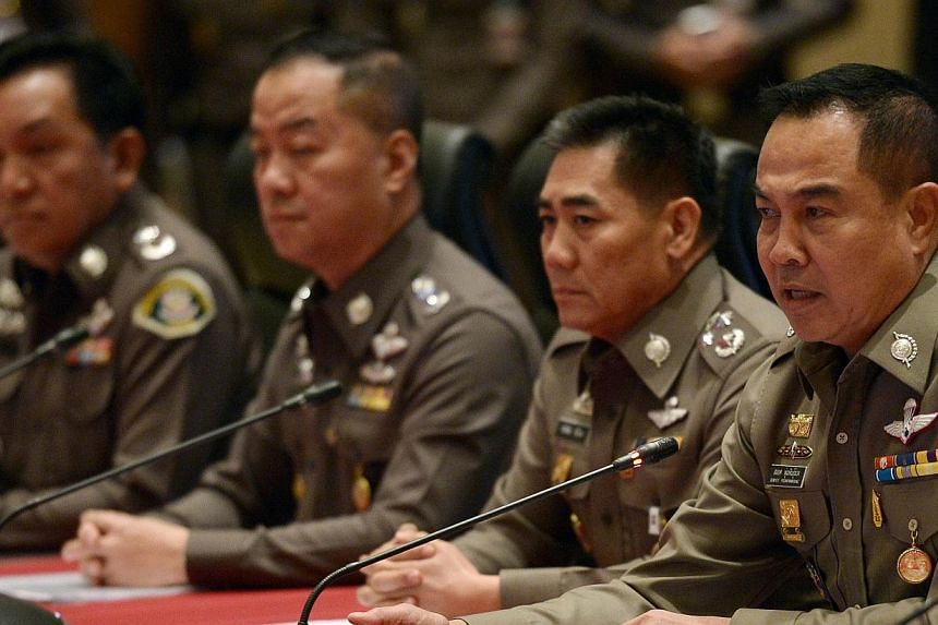 "Thai national police chief Somyot Poompanmoung (right) addresses reporters during a press conference at the Royal Thai Police headquarters in Bangkok on Nov 25, 2014. The Thai junta on Wednesday, Dec 17, 2014, said it will ""hunt"" fugitives wante"
