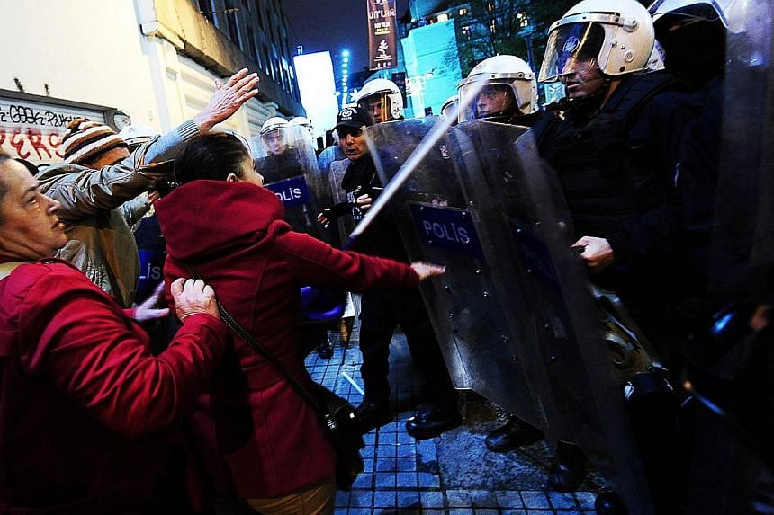 Turkish riot police hold shields to push back protestors demonstrating against attacks launched by the Islamic State in Iraq and Syria targeting the Syrian town of Kobane, on Dec 1 ,2014, in Istanbul. A 17-year-old boy was shot dead during armed