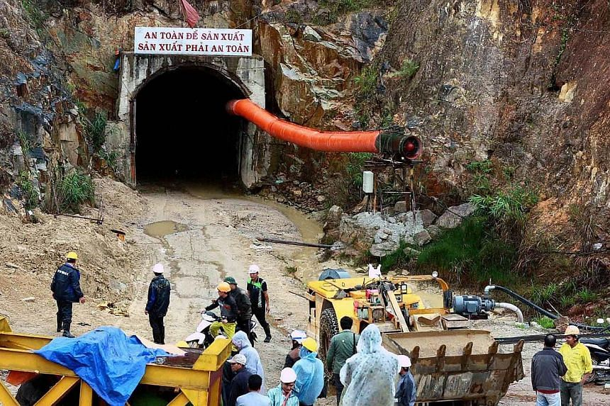 Workers and rescuers stand in front of the entrance of a tunnel at the Da Dang- Da Chomo hydroelectric power plant in Lac Duong district, central highland province of Lam Dong on Dec 16, 2014. Vietnamese rescuers battled on Wednesday, Dec 17, to