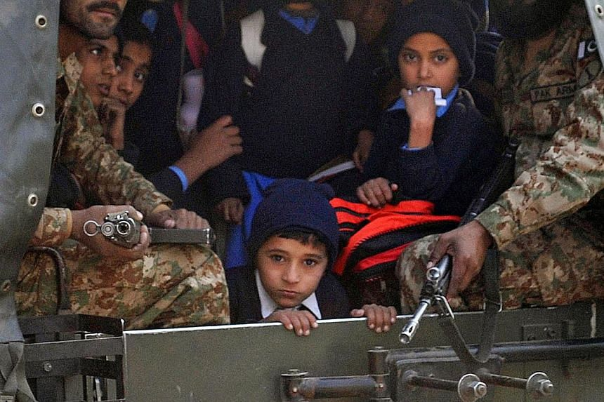 Pakistani soldiers transporting rescued school children from the site of an attack by Taleban gunmen on a school in Peshawar on Dec 16, 2014. -- PHOTO: AFP