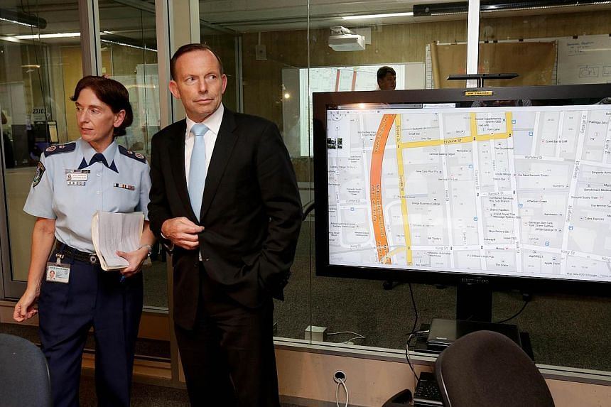 Australian Prime Minister Tony Abbott (centre) meets deputy commissioner Catherine Burn (left) as he visits the Police Operations Centre in the wake of the siege on a cafe in Sydney. -- PHOTO: AFP