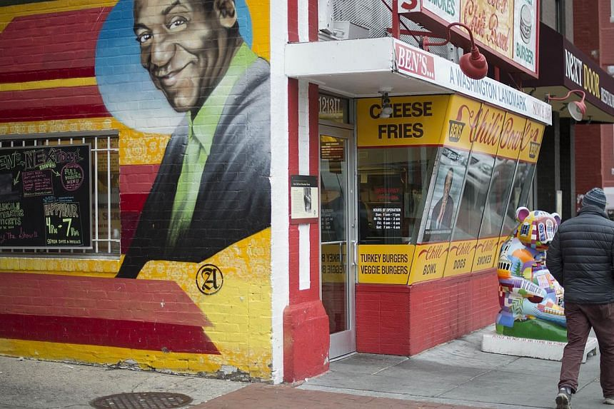 A man walking past a mural of comedian Bill Cosby painted on the side of Ben's Chili Bowl in Washington, DC, on Dec 4, 2014. Prosecutors cited the statute of limitations in declining to pursue the case brought by former Playboy hostess Judy Huth earl