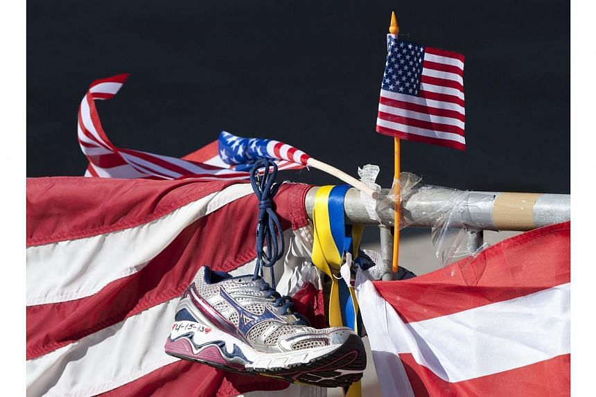 A running shoe and US flag as part of a memorial on the Boston Marathon route in Boston on April 18, 2013. -- PHOTO: AFP