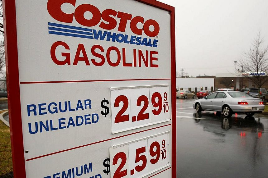 Cars lining up for regular petrol at the Costco in Beltsville, Maryland, on Dec 16, 2014. US stock index futures fell on Tuesday as a slide in the Russian rouble and crude oil prices sent traders fleeing risky assets. -- PHOTO: REUTERS