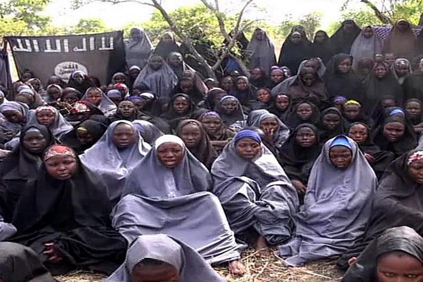A screengrab taken on May 12, 2014, from a video released by Nigerian Islamist group Boko Haram, is thought to show schoolgirls abducted by the group from Chibok, northeastern Nigeria. Schools such as the one in Peshawar, Pakistan where more tha