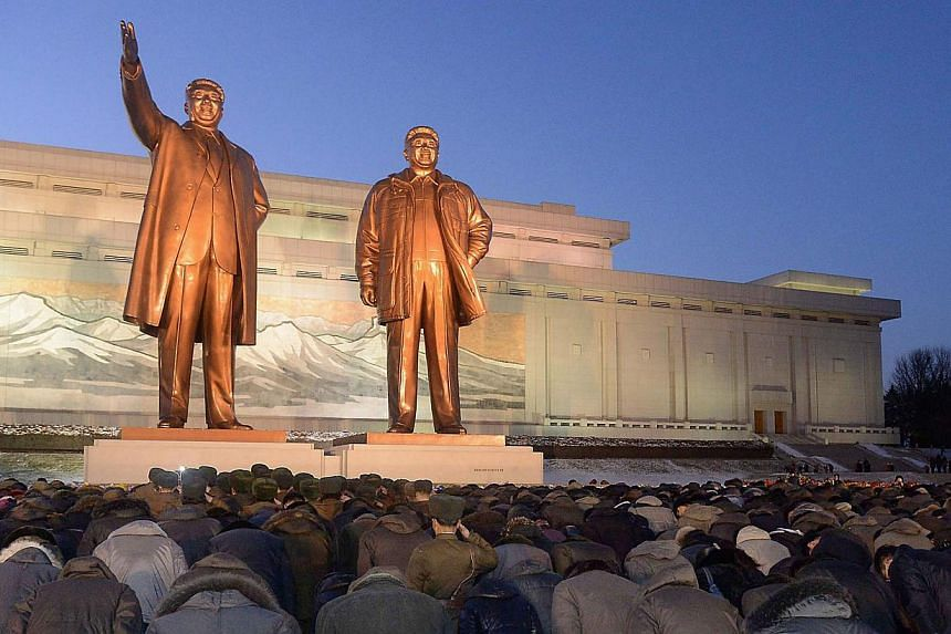 North Koreans bow to bronze statues of late North Korean leaders Kim Il Sung (left) and Kim Jong Il at Mansudae in Pyongyang. -- PHOTO: REUTERS/KYODO