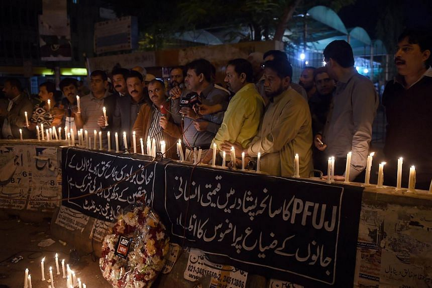 Pakistani journalists light candles for the victims of an attack by Taleban gunmen on a school in Peshawar, in Karachi on Dec 16, 2014. -- PHOTO: AFP