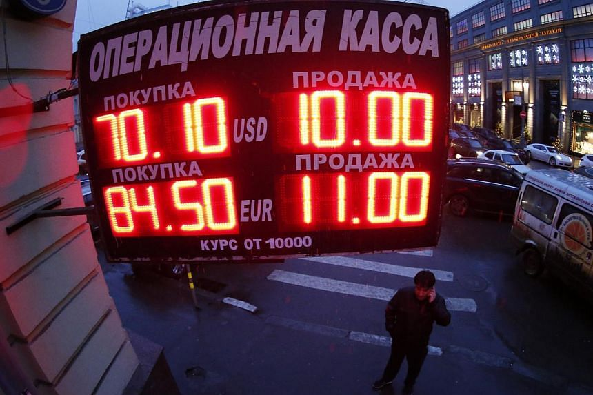 A man standing under a board showing currency exchange rates in Moscow on Dec 16, 2014. The Russian rouble crashed back to earth after an emergency hike in interest rates provided only fleeting support. -- PHOTO: REUTERS