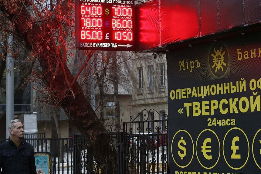A man walks past a building and a board showing currency exchange rates in Moscow, Dec 16, 2014.At the exchange points that are a fixture across the Russian capital, those in need of dollars to protect their savings from the rouble collapse wer