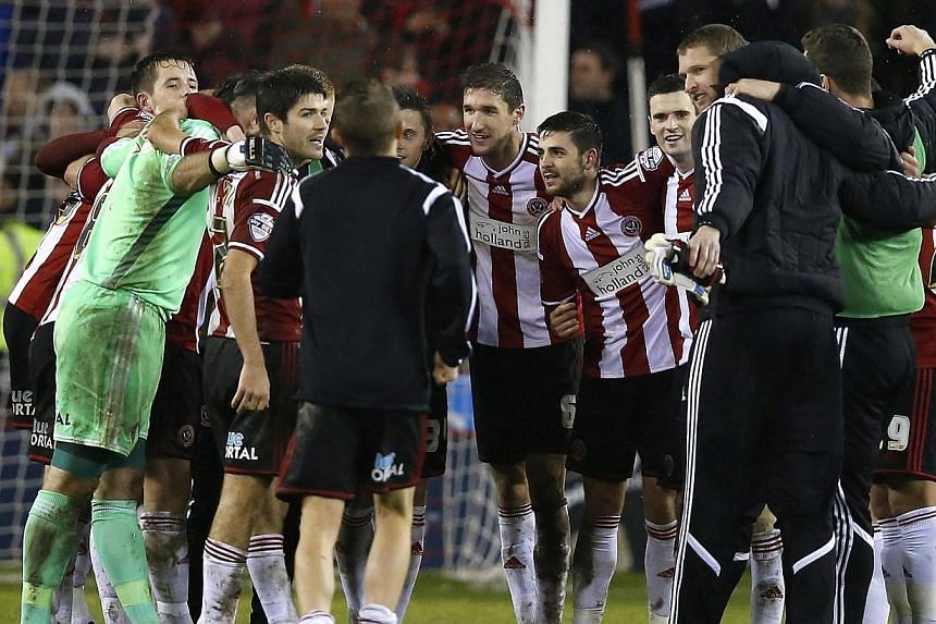 Sheffield United players celebrate after beating Southampton at Bramall Lane in the League Cup. -- PHOTO: REUTERS