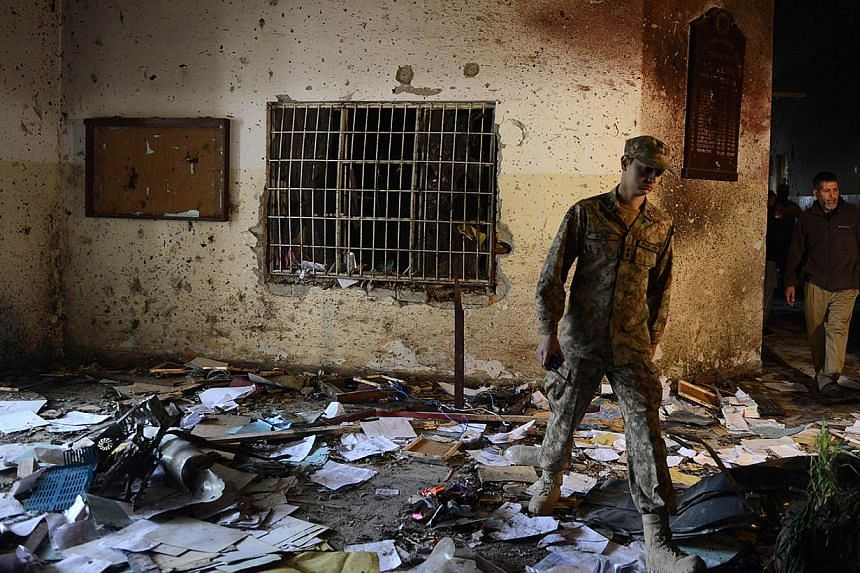 A Pakistani soldier walks amidst the debris in an army-run school a day after an attack by Taleban militants in Peshawar on Dec 17, 2014. Militants rampaged through an army-run school in the north-western city of Peshawar and killed at least 141 peop