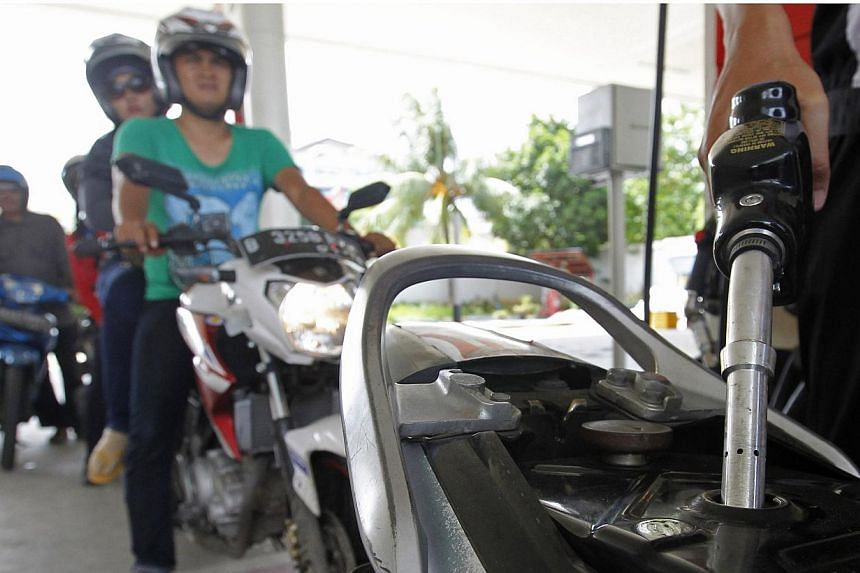An employee of state-owned Pertamina refuelling a motorcycle at its petrol station in Jakarta on Dec 17, 2014. -- PHOTO: REUTERS