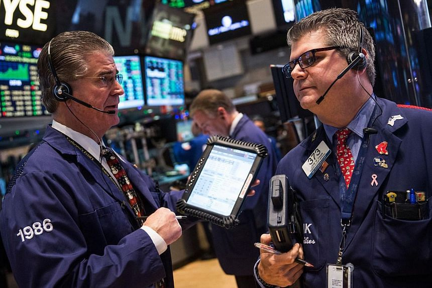 Traders work on the floor of the New York Stock Exchange on Dec 17, 2014. Economists at Wall Street's biggest banks remain convinced the Federal Reserve will raise interest rates by next June and most expect the Fed to tighten policy more than once i