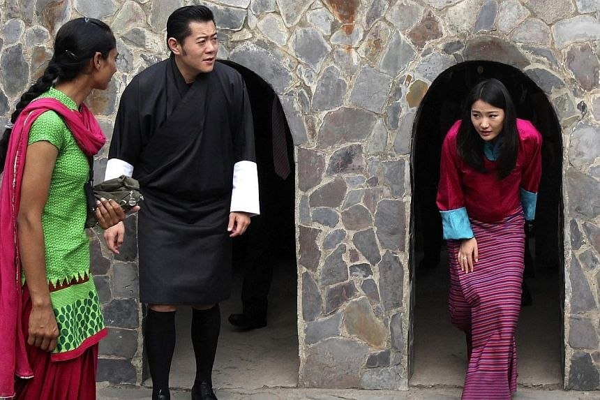 Bhutan's King Jigme Khesar Namgyel Wangchuck (2nd from left) and Queen Jetsun Pema (right) emerge from arch-shaped passages as they visit the Rock Garden in the northern Indian city of Chandigarh Oct 5, 2014.The king of Bhutan on Thursday urged