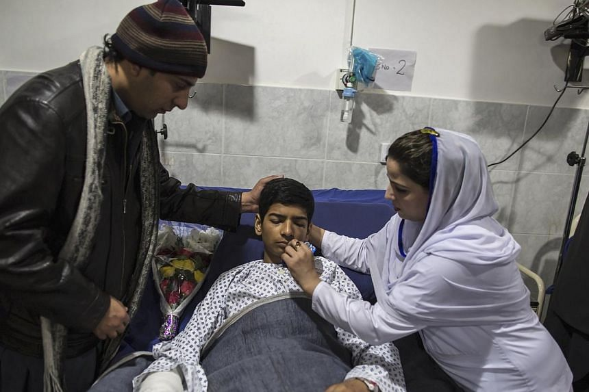 Mehran Khan, 14, who survived an attack by Taliban gunmen on the Army Public School, received his medicine as he lies on a hospital bed in Peshawar on Dec 17, 2014.Students grieving for their classmates massacred by the Pakistani Taleban Thursd