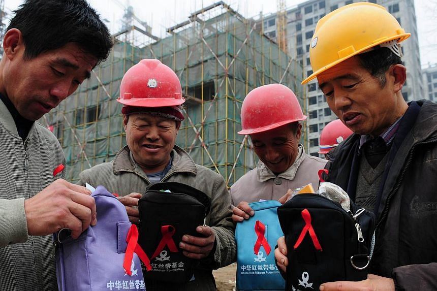Migrant workers receiving health packages from volunteers in Liaocheng, Shandong province, on Nov 30, 2014. The World Health Organisation issued a call to action to China on Dec 1, 2014 over HIV/Aids as government figures said nearly half a million p
