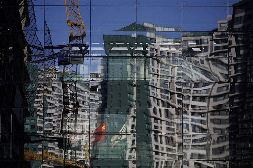 A construction site and a residential building reflected on the glass wall of a building in Beijing on Dec 15, 2014.  China's home prices fell in November for a third consecutive month versus year-ago levels, pointing to a persistent property do