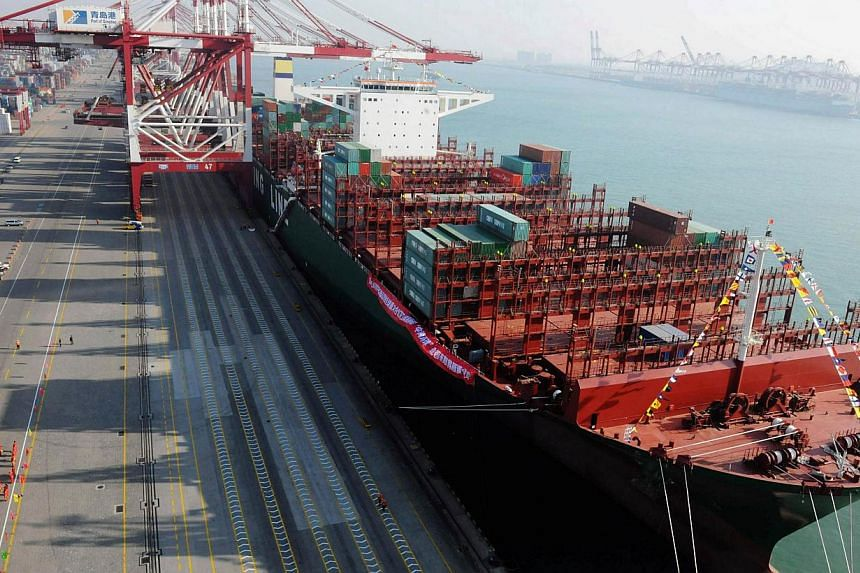 The CSCL Globe at Qingdao port on Dec 4, 2014. The world's largest vessel by container volume made its maiden call on Singapore on Thursday. -- PHOTO: AFP