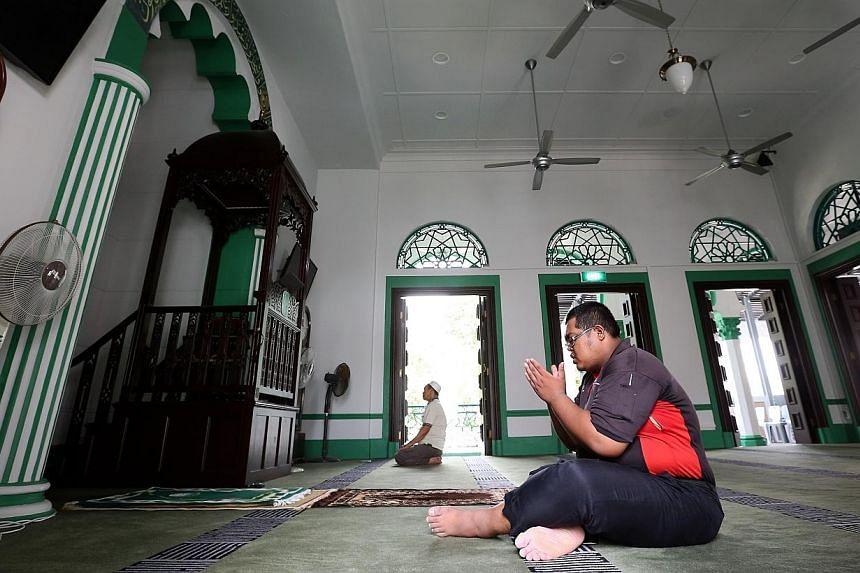 Mr Mohammed Irwan Abdul Wahid (in black), 31, prays in the main prayer hall of the Alkaff Upper Serangoon Mosque on Dec 18, 2014. -- ST PHOTO: NEO XIAOBIN