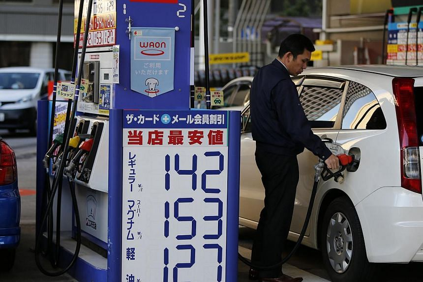 A man refuels a vehicle at a petrol station in Tokyo on Dec 17, 2014. Oil prices edged higher in Asia Thursday after data showed US stockpiles dipping, while the Federal Reserve indicated interest rates would not be hiked until the middle of next yea