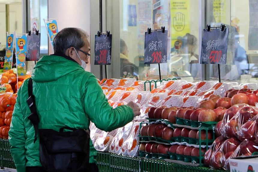 An elderly man a food supermarket in Tokyo on Dec 8, 2014. Japan will spend over 3 trillion yen (S$33 billion) in a stimulus package aimed at reviving regional economies hit by slumping household spending after a sales tax hike in April. -- PHOTO: AF