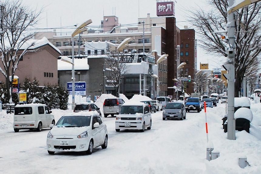 Vehicles are seen on a snow-covered street in Obihiro in Japan's northern island of Hokkaido on Dec 17, 2014. -- PHOTO: AFP