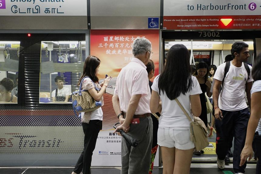People waiting to enter the train at Dhoby Ghaut MRT station along the North-East line during peak hour. By the end of next year, all MRT stations on the North-East Line and 12 more stations on the North-South Line and East-West Line will offer free