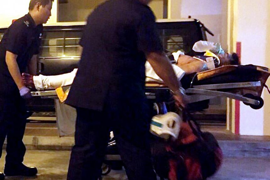 A person believed to be the suspect in the the alleged murder of a woman at a HDB block in Tampines is attended to by paramedics on Dec 17, 2014. -- PHOTO: SHIN MIN