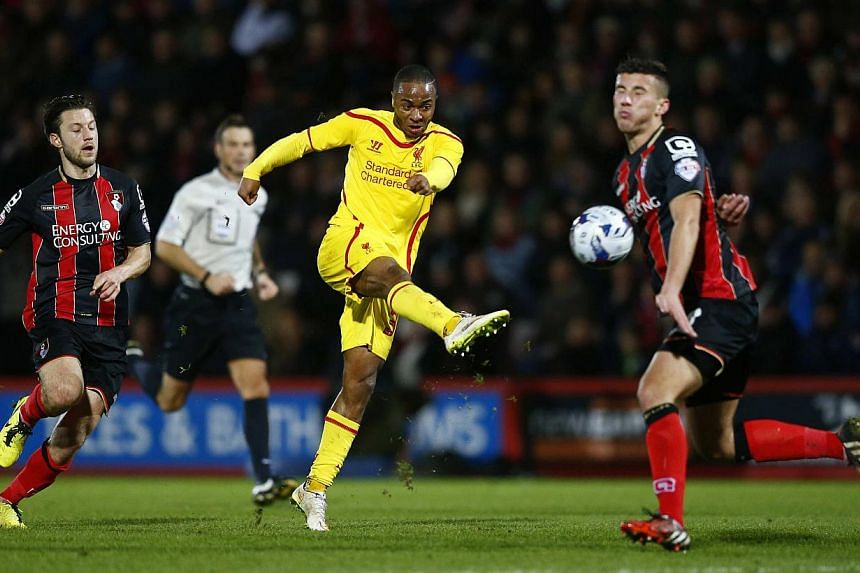 Raheem Sterling of Liverpool shoots past Baily Cargill of Bournemouth during their English League Cup quarter-final soccer match at Goldsands Stadium in Bournemouth, southwest England on Dec 17, 2014.