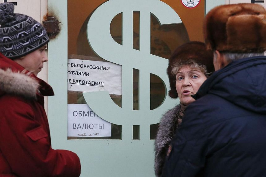 People gathering near a currency exchange office in Moscow on Dec 17, 2014. The US dollar rose on Thursday after the Federal Reserve signalled it was on track to raise interest rates next year. -- PHOTO: REUTERS
